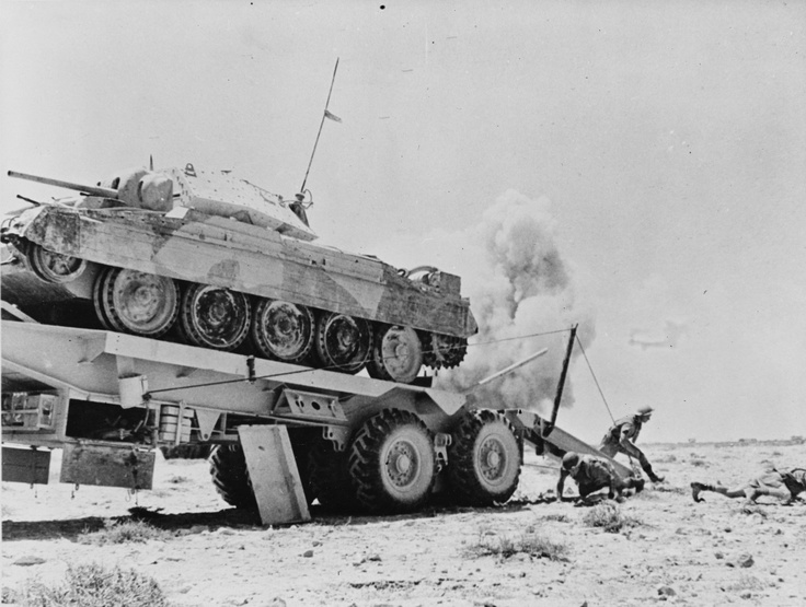Western Desert, 1942: British tank recovery crew scrambles for cover as German gunners open up in the direction of the recovery location. The crew has just loaded a disabled Crusader tank onto the flatbed.
