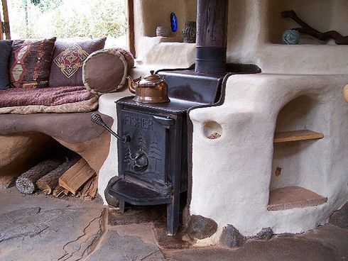 Cob lessons: The wood stove is surrounded by cob for thermal mass, and includes a warm nook with shelf to culture yogurt.