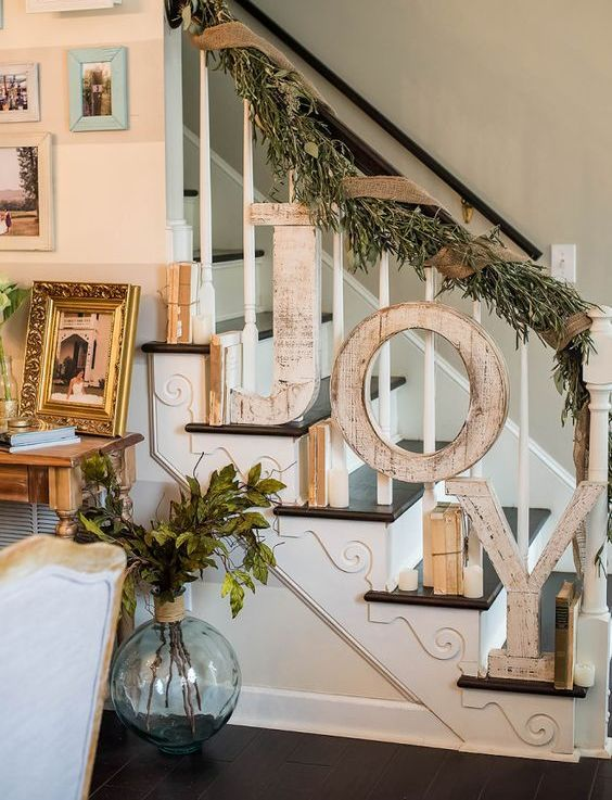 shabby wooden JOY letters attached to the banister and a foliage and burlap garland