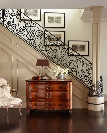 GORGEOUS wrought iron staircase...and is that a 'Hooker' piece of furniture at the bottom of the staircase?