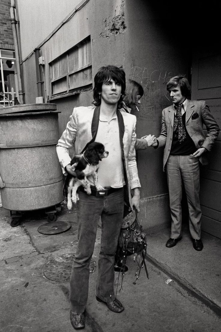 """This Dog in History: On May 13, 1965 The Rolling Stones recorded their hit song """"Satisfaction."""" Here's Keith Richards holding Mick Jagger's dog, a king Charles spaniel puppy, Boogie in 1971."""