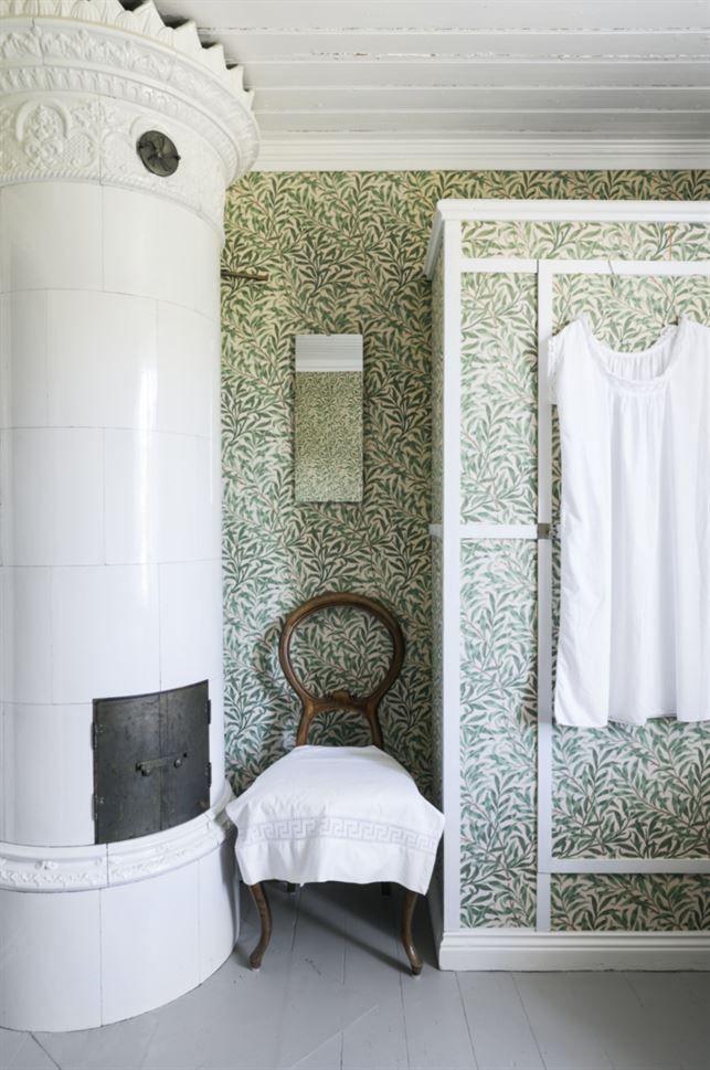 Gröna väggar. Gästrummet i grönt har också en kakelugn som går att elda i. Garderoben har blivit klädd med samma tapet som väggarna.