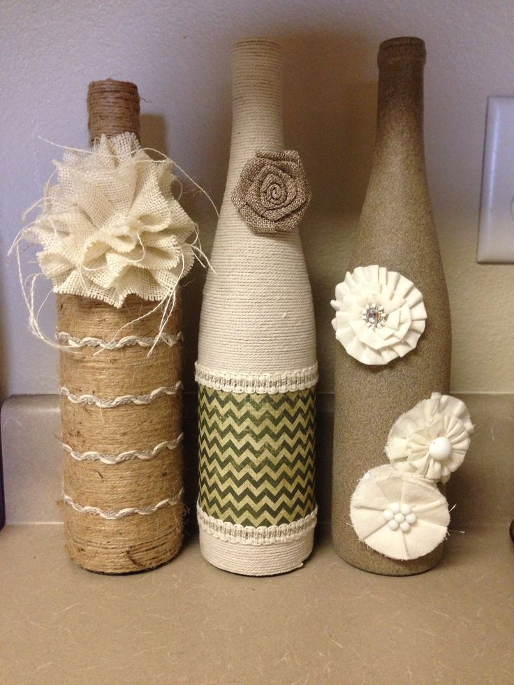 Decorated wine bottles with twine, textured spray paint, scrapbook paper, and decorative flowers