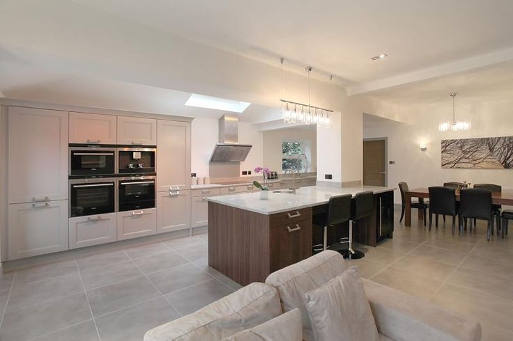 photo of open plan beige grey white flagstones veneer dining room kitchen with lighting and bar stools