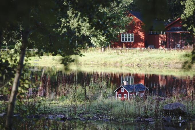 Miniature wooden house on pond, traditional house in background, Aland Islands.