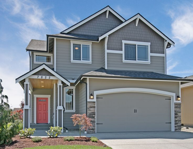 Diamond Plan. Grey exterior with white trim. Black gutters and a bold Coral front door. Carriage style garage doors and stone accents make this a great traditional or craftsman style home.