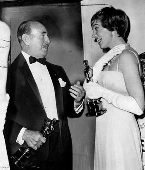 """Jack Warner, holding his 1965 Best Director Oscar for """"My Fair Lady"""" congratulates Julie Andrews, who is holding her Best Actress Oscar for """"Mary Poppins"""". Julie starred on Broadway in """"My Fair Lady"""" as Eliza Doolittle; however, in  the movie version Eliza was played by Audrey Hepburn."""