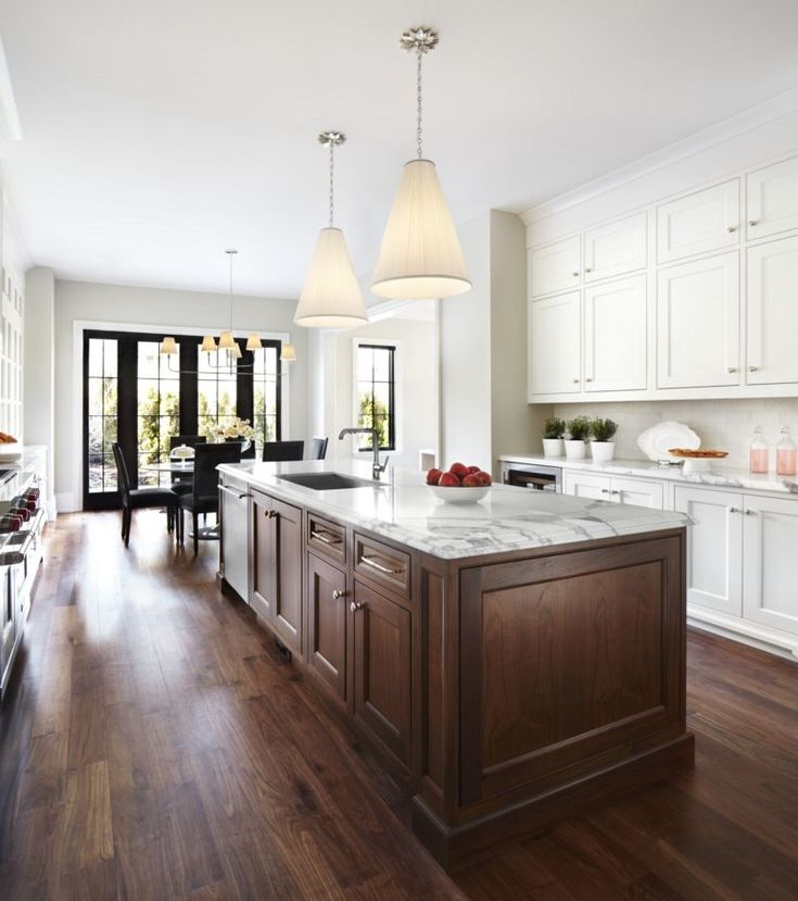 Two-tone cabinets with hardwood floors & black mullioned windows & doors. Love the wood island with white cabinets