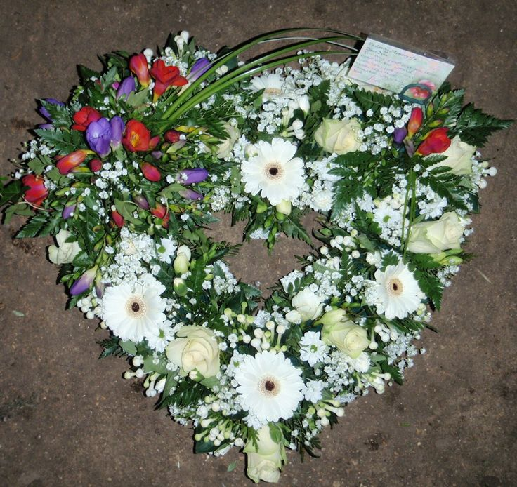 an open loose heart wreath made with white flowers, and includes a small colourful freesia spray in top left corner