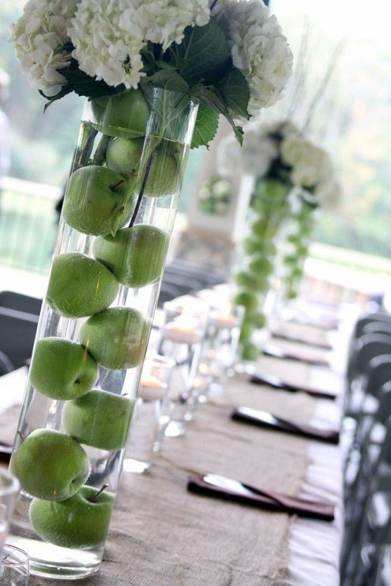Really digging the asymmetrical look of the apples - a wrap of black damask ribbon at the top would be cute to dress up the vase and hide any flower stems. megme