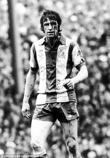 West Bromwich Albion's John Wile plays on despite the blood gushing from the wound on his forehead