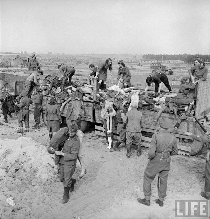 Male & female German SS soldiers being forced to load corpses onto trucks under British guard at the Bergen Belsen concentration camp. Location: Bergen Belsen, Germany   Date taken: May 1945   Photographer: George Rodger