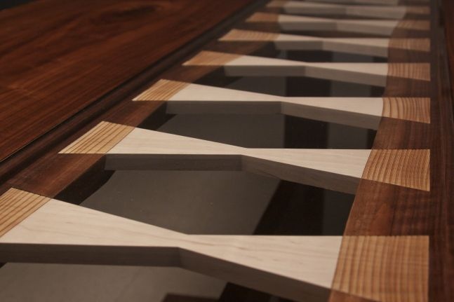 Laser-engraved maple dovetail splines in a live-edge walnut table