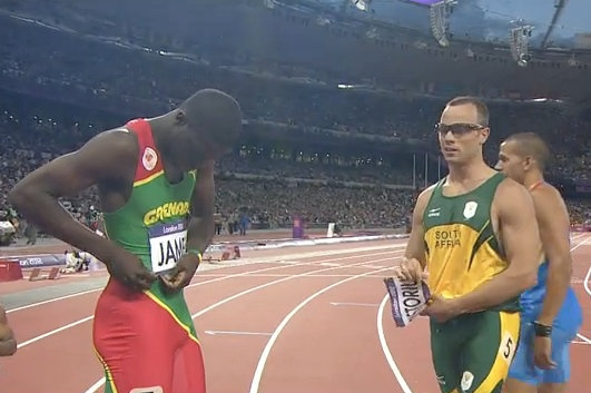 Kirani James and Oscar Pistorius exchange bib numbers after completing in 400 meters semifinal