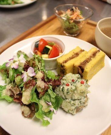 「畑のリーフレタスサラダ」。 柔らかくて味が濃くて本当に美味しい。 玉ねぎドレッシングをかけて盛りつけました。 小さな可愛らしいお花は大根の花。 ほんのりと大根の味。 手前は「じゃが芋の豆腐マヨネーズ和え」。 マスタードや白味噌、りんご酢、オリーブオイルで作る豆腐マヨネーズに 青さ海苔を加えて柔らかくマッシュしたじゃが芋を和えました。 ピンクペッパーをトッピング。 奥のサンドイッチ風は「さつま芋豆腐の車麩サンド」。 さらに黄色をきれいに出すためにターメリックを加えました。 ココットには「ミニトマトとズッキーニの中華風ドレッシング和え」。 豆板醤を少量加えた中華風ドレッシング。 胡麻油、醤油、米酢、甜菜糖で作ります。