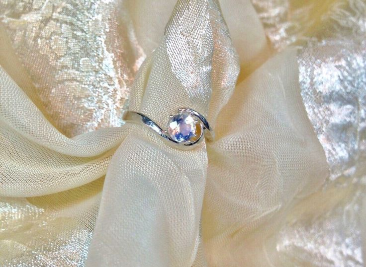 A personal favorite from my Etsy shop https://www.etsy.com/listing/173144342/swirl-engagement-ring-rainbow-moonstone