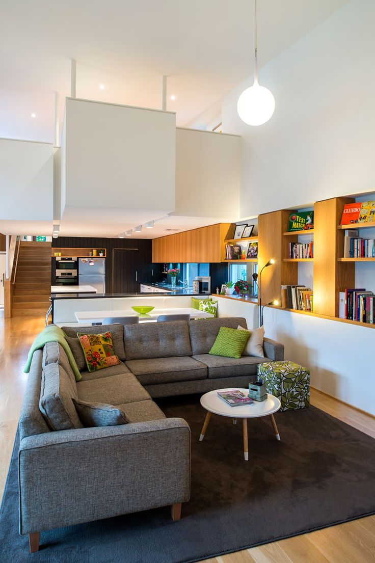 This casual living area has wood shelving and cabinets that run along the wall and lead into the kitchen.