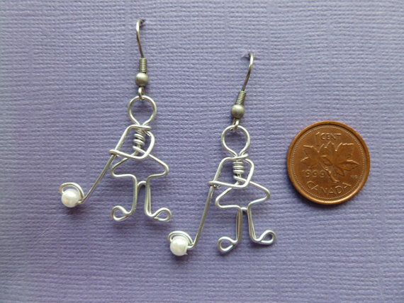 These are cute golfing earrings. They are golfing ladies. These are very original! This unique design was created by drawing it first, and then with a LOT of practicing, made with wire. They are a bit more than 1 inch in size. (check the coin photo). They are made of a wire that wont tarnish. The golf stick has a white bead. The hooks are nickle-free so there are no problems for people who have allergies. I will put a stopper on the hooks also so you dont loose them!! A must for golf…