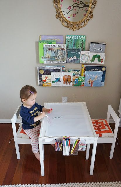 Table and chairs for kids. Book shelf on wall. Pot of crayons and paper