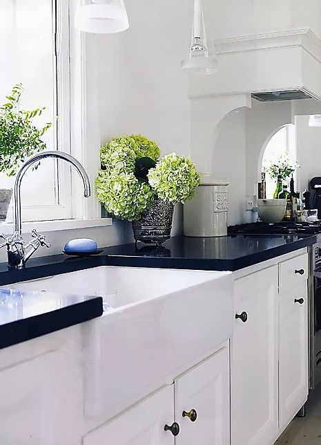 white kitchen cabinets, farmers sink, and black countertops