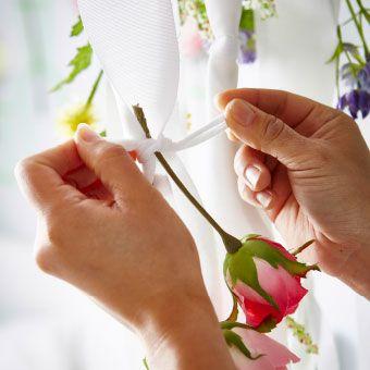 リボン状にカットしたホワイトのカーテンに造花を結び付ける人。