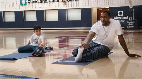 A student from Holy Cross Elementary school in Euclid shares a moment of yoga stretching with LeBron James during a February visit of children to the Cavaliers' training facility in Independence. Description from cleveland.com. I searched for this on bing.com/images