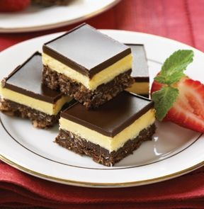 """NANAIMO BARS. These bars will satisfy any sweet tooth – original flavour is a custard filling, layered between a base of coconut graham cracker crumbs and cocoa, topped with chocolate icing. 5""""x12"""" tray. - M & M Meat Shops"""