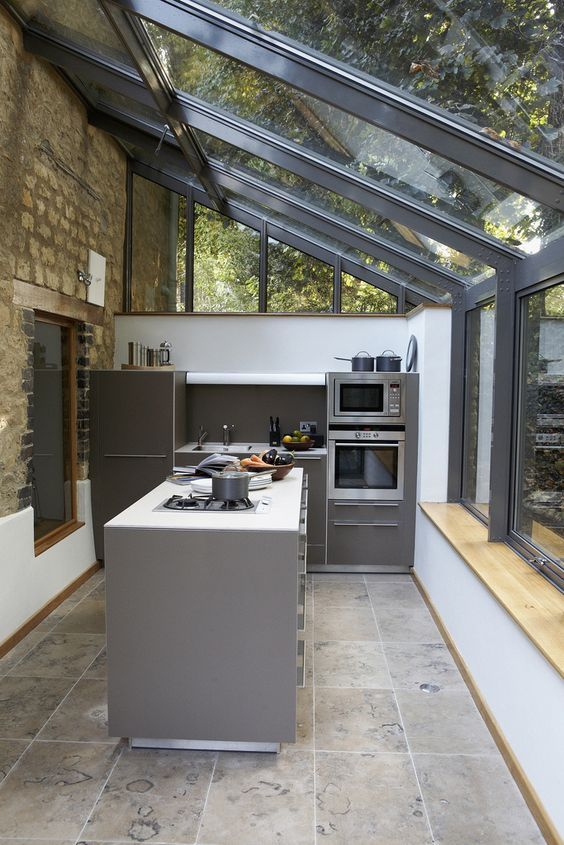 This industrialised kitchen extension blends brilliantly with the period feel of it's listed host building; complimenting the brick work whilst remaining unafraid to claim an identity of it's own through the use of masculine grey powder coasted aluminium and a stainless steel kitchen design. The lean-to design of this structure works well; encapsulating the views of nature both across the garden space as well as from above as the canopy of trees shades the roof from extra heat.   For more…