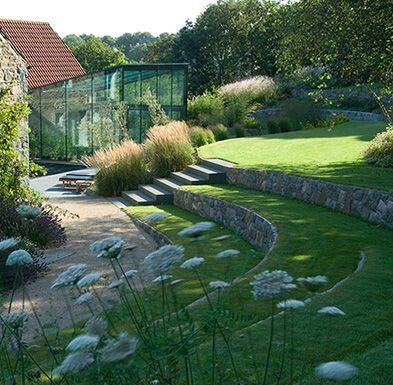 Carefully curved stone risers with lawn terraces. Modern glass green house, drifts of ornamental grasses