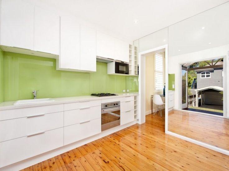 White kitchen and timber floors with a nice apple green glass splashback. #kitchesplashback #glasssplashback #timberflooring #green