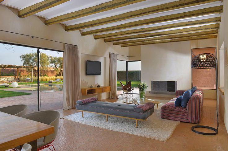 Le living room. Ouvert sur le jardin et la piscine. Des rondins d'eucalyptus au plafond. Une photo Beachcomber.