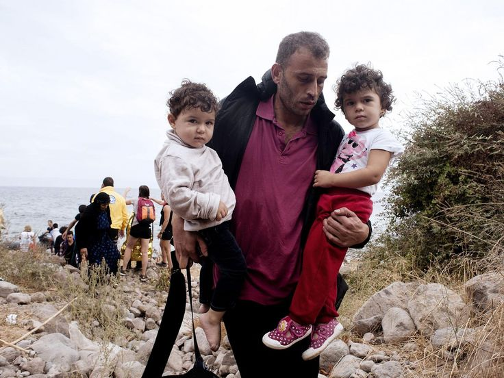 A refugee carrying his children walks on Sykamia beach, west of the port of Mytilene, on the Greek island of Lesbos after crossing the Aegean sea from Turkey on September 22, 2015