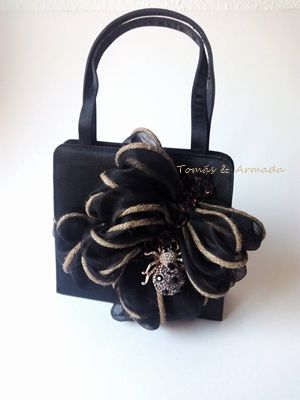Bolso de raso negro decorado con cinta de organza con hilo de cáñamo .