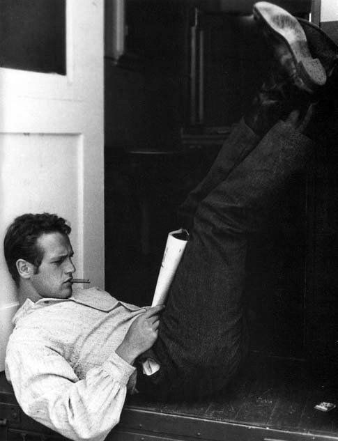 paul newman // whit a glass of wine next to him.