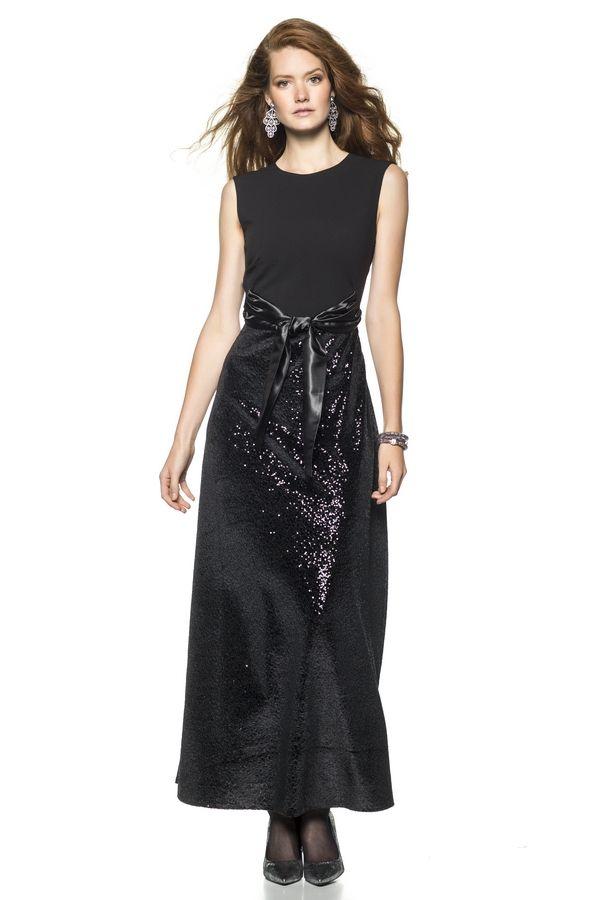 Maxi-jurk met slank getailleerd lijfje van crêpe, met schuine coupenaden waartussen strikbanden zijn genaaid. Een uitlopend rokdeel zonder (coupe)naden. Achter een V-hals met overslageffect.