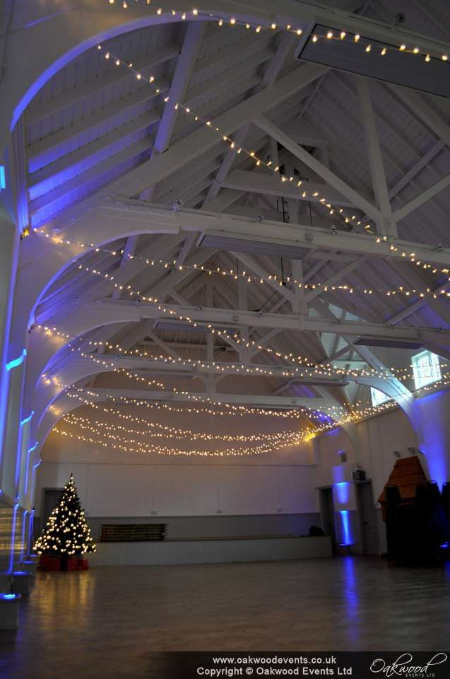 Crossed strands of fairy lights and uplighting at Hastoe village hall