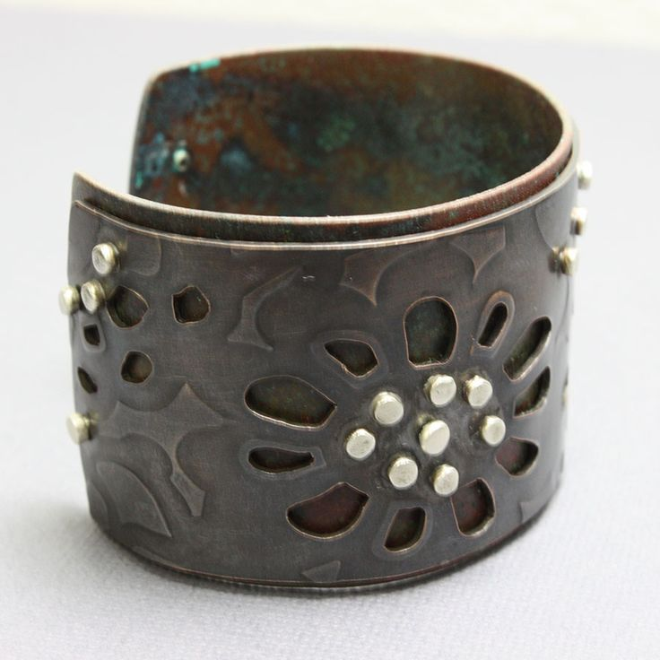 Copper and sterling silver cuff. I have handmade this copper cuff in my studio. It is actually two pieces of copper permanently riveted together with sterling rivets. The top cuff has been rolled, pie