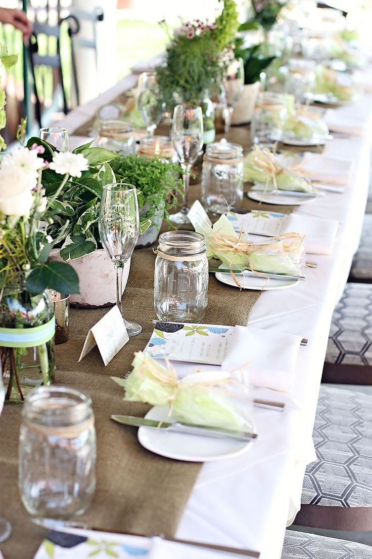 the merging of rustic features like burlap runners and mason jar cups with the elegant champagne stemware and ribbon place setting