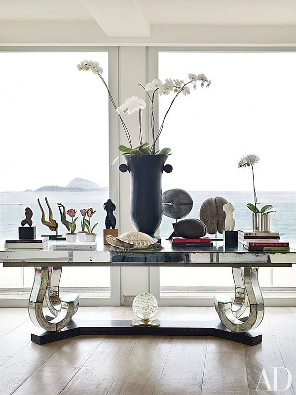 At the Rio de Janeiro home of late designer Alberto Pinto, a Marcel Coard table hosts an ivory turtle, an Art Deco vase, and sculptural coco de mer seeds in the living room | archdigest.com