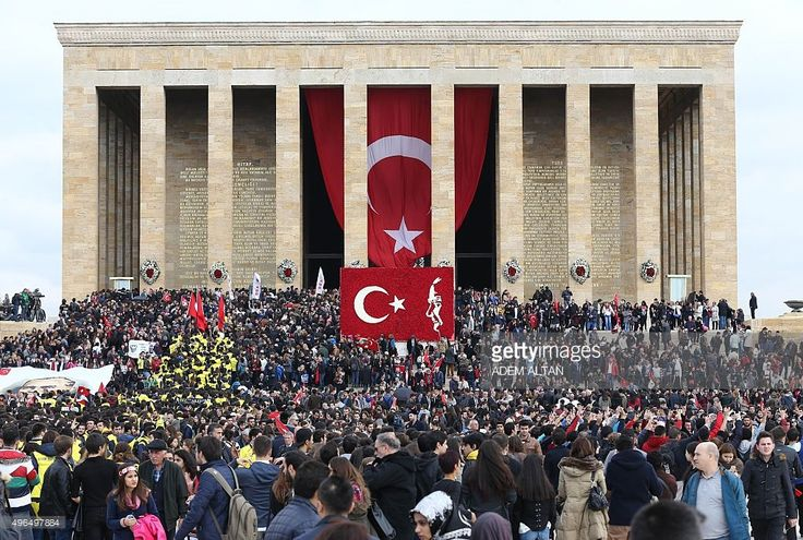 People hold-up the national flag as they gather outside the Anitkabir, the mausoleum of Mustafa Kemal Ataturk, founder of the Republic of Turkey, during the 77th anniversary of Ataturk's death in Ankara, on November 10, 2015.