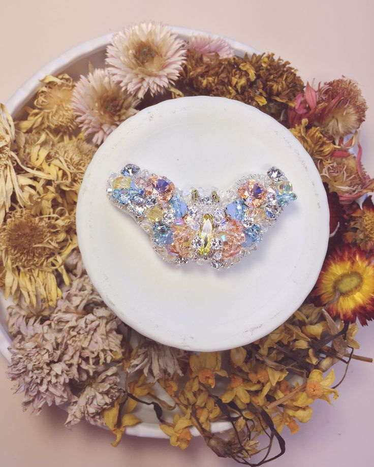 Dedicated to a truly beautiful woman, inside and out - this intricately embellished butterfly brooch reflects not just her vibrant personality but also her strength, courage and compassion. Sparkling hues of @swarovski crystals in tones of light peach, yellow and aquamarine mixed together with shining moonlight crystals for a shimmering effect bringing life, spirit and soul into this treasured piece.