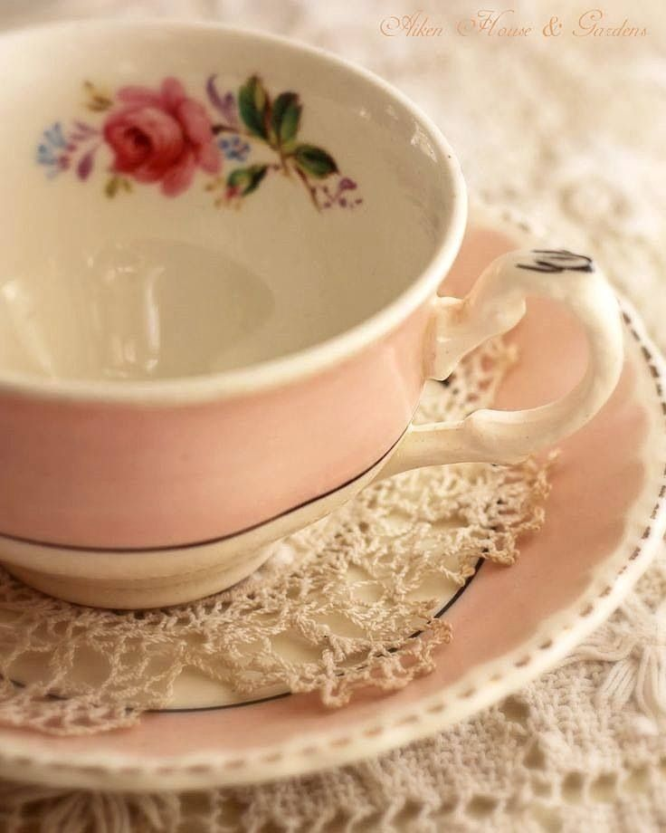 Pretty pink teacup with flowers and doily.