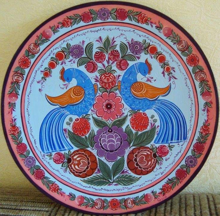 A wooden plate is decorated with folk Gorodets painting from Russia. #art #folk…