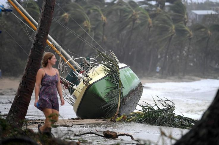 A local resident walks past a yacht that was washed ashore in Airlie Beach. AAP/Dan Peled/via REUTERS