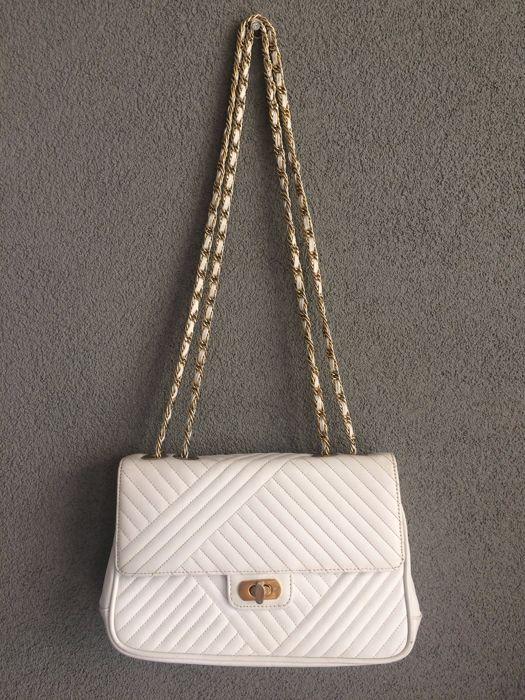 Laïmbock - Schoudertas Prachtige doorgestikte wit leren tas van het mooie merk Laïmbock.De tas heeft 4 vakken en nog een kleiner vakje met een rits. Over 3 van deze vakken valt een klep en over deze vakken en het 4e vak valt de klep van de tas. (zie de foto's). Deze klep wordt vastgezet met een goudkleurige draaisluiting. Op het vakje met rits is een goudkleurig plaatje met de naam Laïmbock bevestigd. Het schouderhengsel bestaat uit een goudkleurige schakelketting waardoor een wit leren…