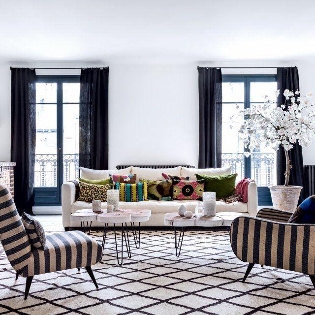 Dans ce salon noir et blanc, on marche sur un gigantesque tapis berbère en laine, on s'assoit sur un canapé blanc Caravane et on admire l'arbre en fleur de chez SIA.