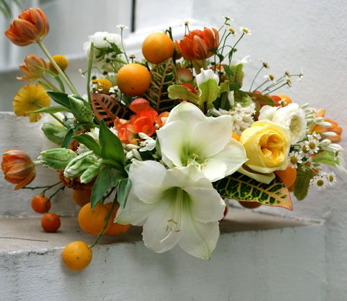 Winter flowers don't have to be drab. This mix of citrus, ranunculus, tulips, croton, lady slippers, camomile and cut begonias scream tropical vacation, just what you're likely to need right now.