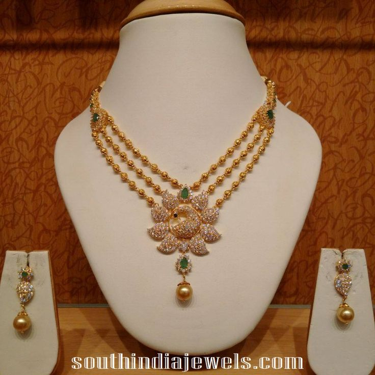 Stunning gold ball necklace set with peacock pendant. The necklace and pendant is studded with precious diamonds and green stones.