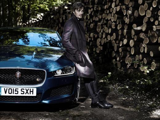 Sam lehnt an seinen Jaguar Sportbrake in einem Pullover von Pal Zileri und einer Hose von Prada, Mantel: Hermès. Schuhe: Santoni.