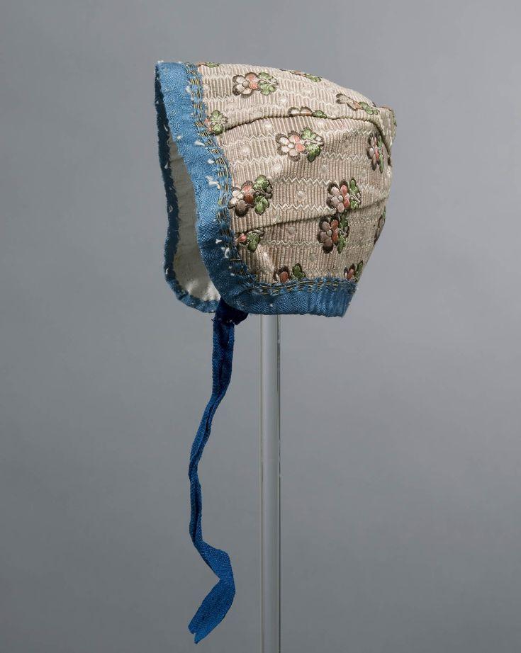 Jongensmuts bestaande uit 6 straalsgewijze pandjes, gemaakt van een gedessineerde zijde en gevoerd met katoen. De muts is rondom afgezet met een zijden bandje waarin gouddraad is verwerkt. #Arnemuiden